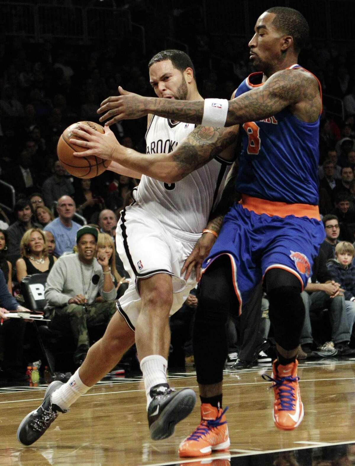 Brooklyn Nets guard Deron Williams attempts to drive around New York Knicks guard J.R. Smith. By The Associated Press