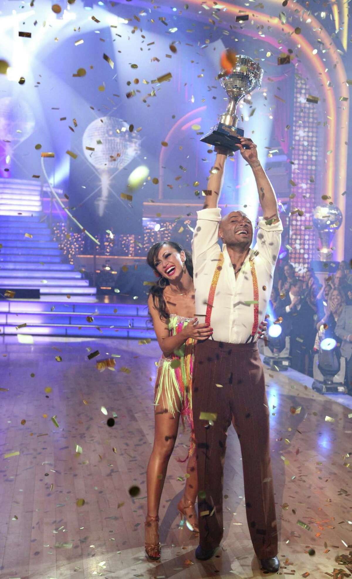 In this image released by ABC-TV, war veteran and actor J.R. Martinez, right, and his partner Karina Smirnoff hold their award after they were crowned champions of the celebrity dance competition series,