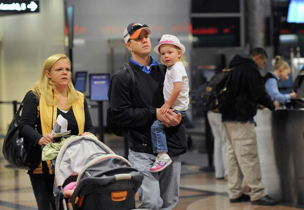 Jen Daley, left, pushes a stroller with daughter Sofia Daley while her husband Scot Daley, center, and daughter Scotlyn Daley, right, 3, all of Centennial, walk to their gate at Denver International Airport on Wednesday. They are traveling to Florida for the Thanksgiving holiday. Associated Press