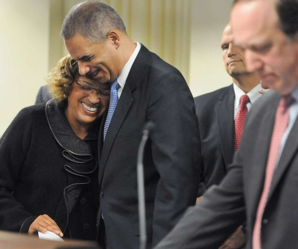 Alicia Caraballo, Adult Education Director for the New Haven Board of Education, left, is hugged by Attorney General Eric Holder after Caraballo shared the loss of her son n to gun violence in New Haven, Conn. during a press conference Tuesday, November 27, 2012 at the United States Attorney District of Connecticut Office in New Haven announcing the launch of Project Longevity, an initiative to reduce gun violence in Connecticut's major cities. At far right is United States Attorney for Connecticut David Fein. Photo by Peter Hvizdak / New Haven Register