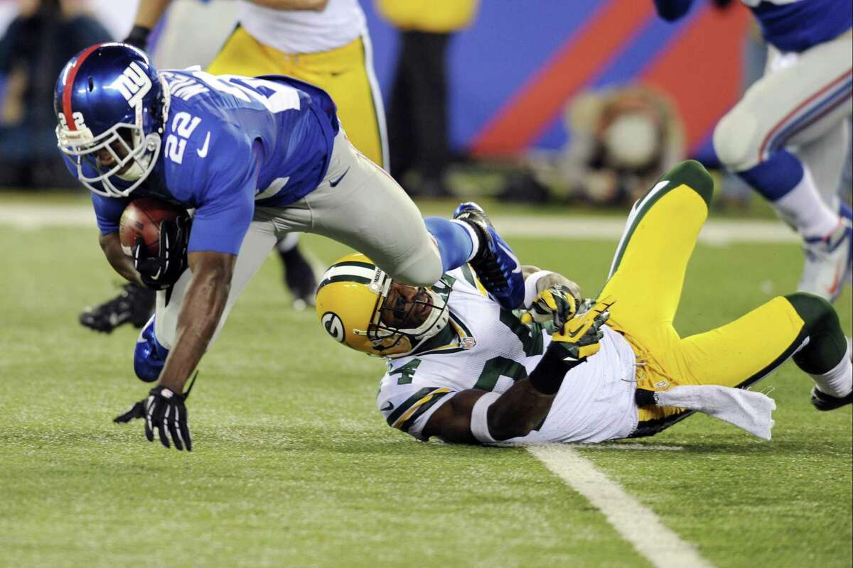 New York Giants' David Wilson is tackled by Green Bay Packers' Jarrett Bush during the first half of the Giants victory Sunday night. By The Associated Press