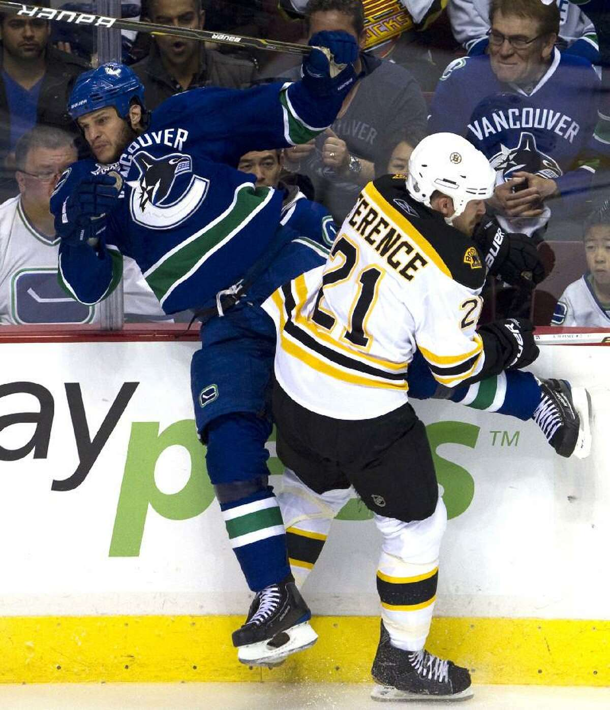 ASSOCIATED PRESS Vancouver's Kevin Bieksa, left, is checked by Boston's Andrew Ference (21) during the first period of Game 1 in the Stanley Cup finals Wednesday in Vancouver, British Columbia. The Canucks won 1-0 to take a 1-0 lead in the series.