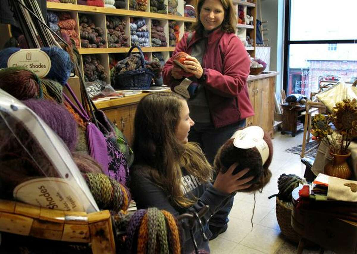Kayla Underkoff, 12 and her mom, Jennifer, shop at In Sheep's Clothing, a yarn shop on Main St. Owner Cheryl Balch says her business of four years is growing. (Debbi Morello / Register Citizen)