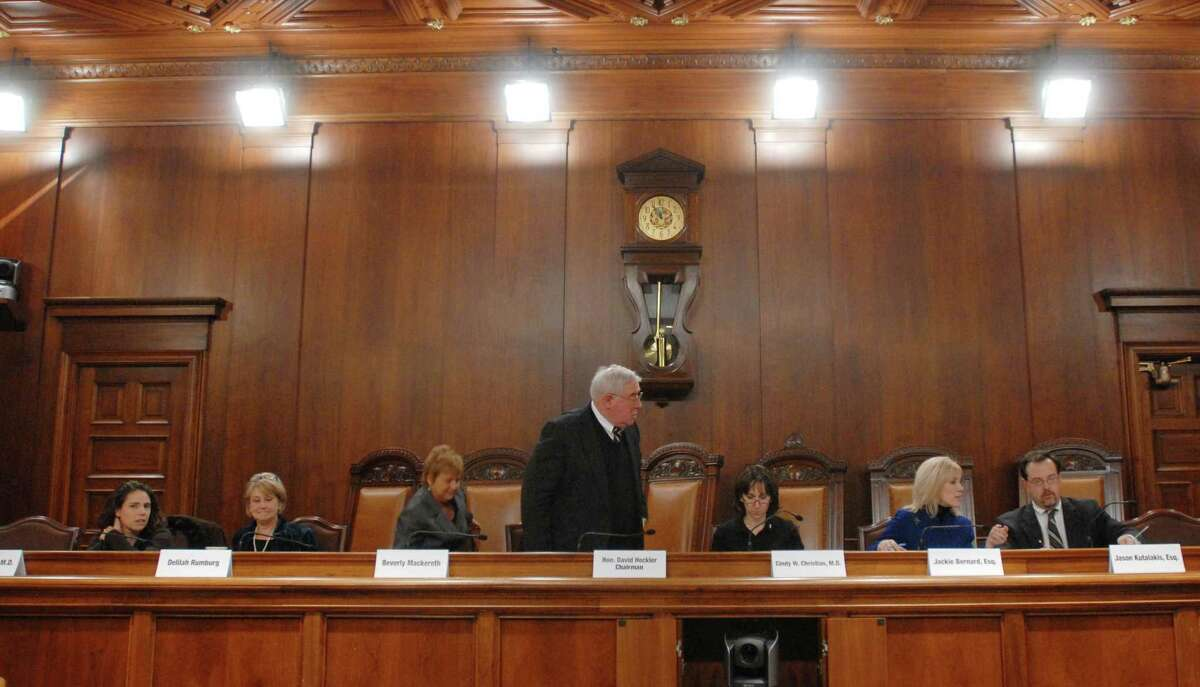 Bucks County District Attorney David Heckler, center, stands, as Commission members, from left, Rachel Berger, MD Delilah Rumberg, Beverly Mackereth, Cindy Christian, MD, Jackie Bernard, and Jason Kutalakis, are seated before a news conference announcing the findings of a report from the Pennsylvania Task Force, on Child Protection Tuesday, Nov. 27, 2012 By The Associated Press