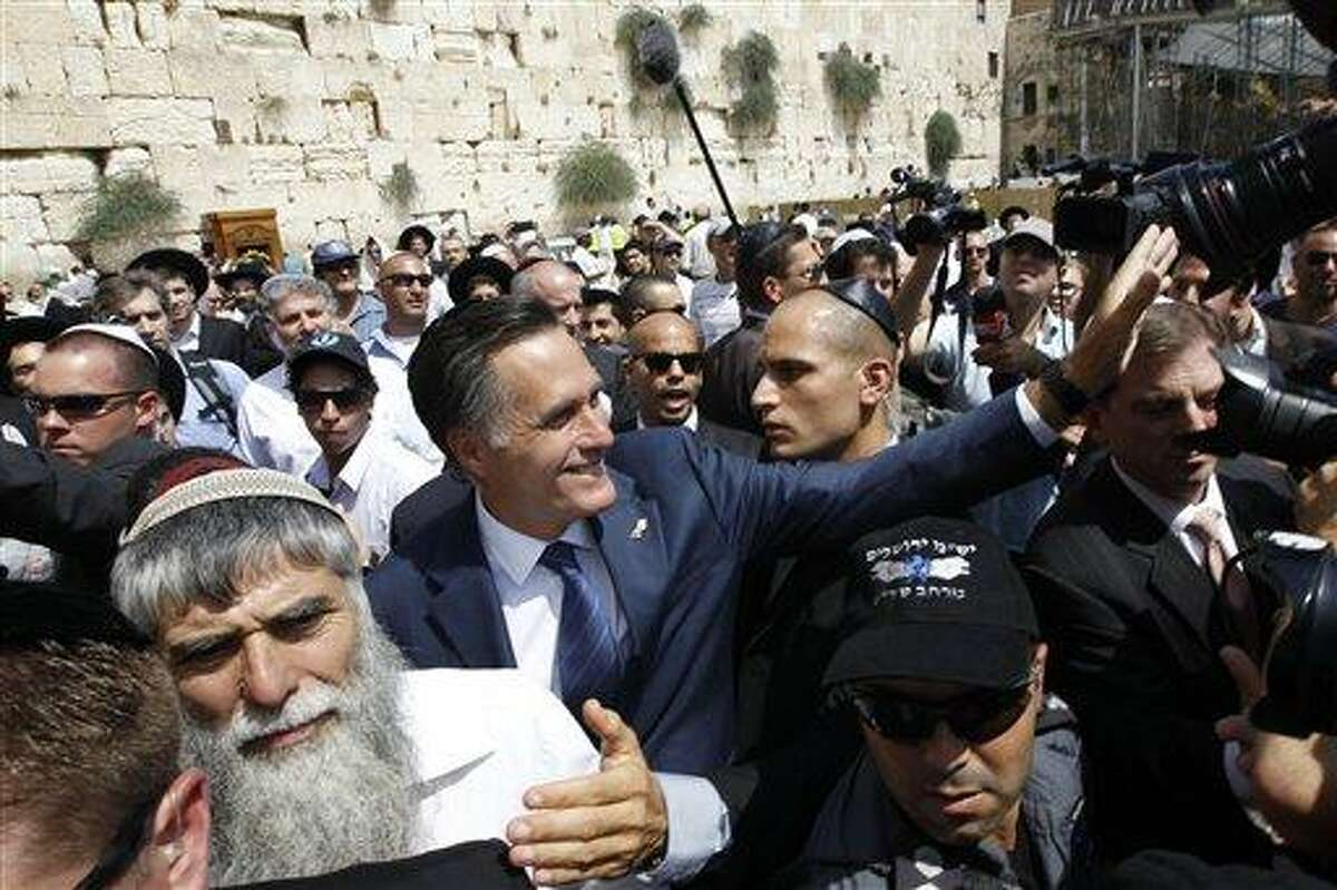 Republican presidential candidate and former Massachusetts Gov. Mitt Romney greets the crowd after he visited the Western Wall, rear, in the Old City of Jerusalem, Sunday, July 29, 2012. Associated Press