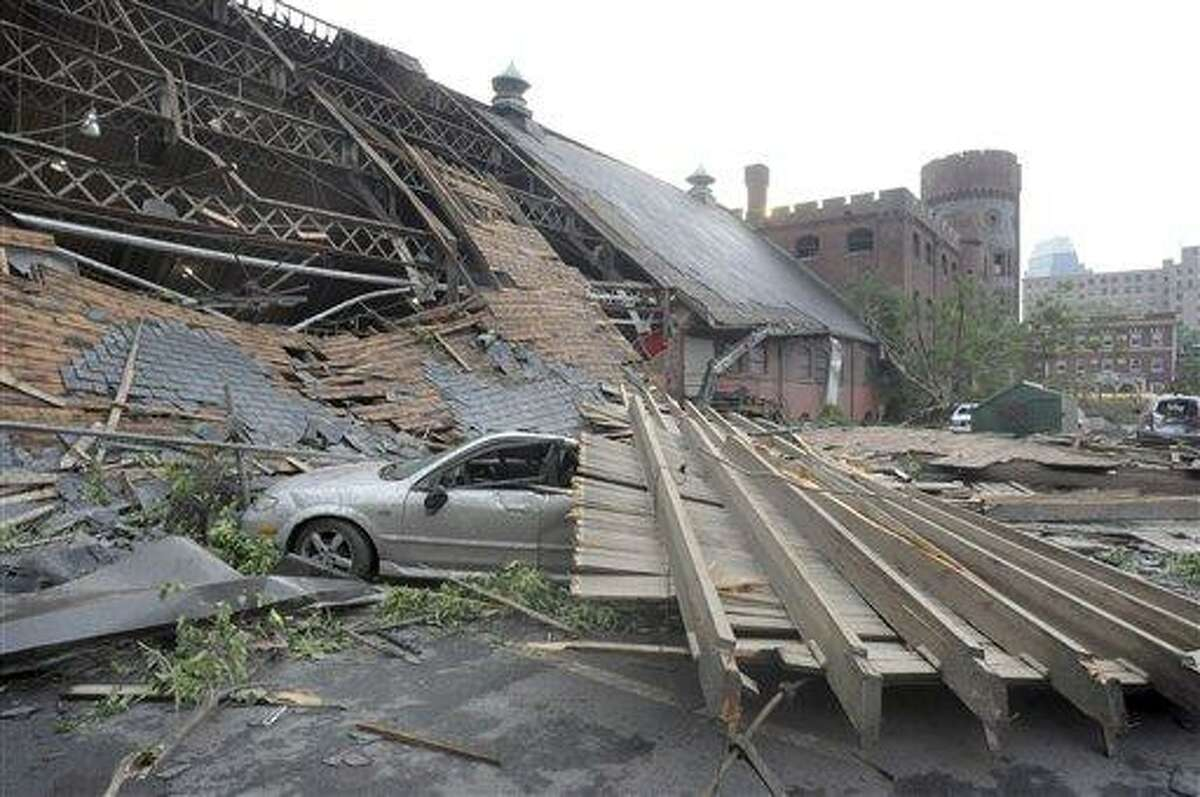 A smashed car sits next to the South End Community Center, which lost most of its roof in a tornado that touched down in Springfield, Mass., Wednesday, June 1, 2011. (AP Photo/Springfield Republican, Michael S. Gordon)