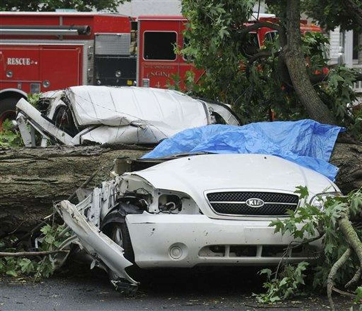 A car sits crushed by a tree on Main Street following a tornado touchdown in West Springfield, Mass., Wednesday, June 1, 2011. (AP Photo/Springfield Republican, Dave Roback)