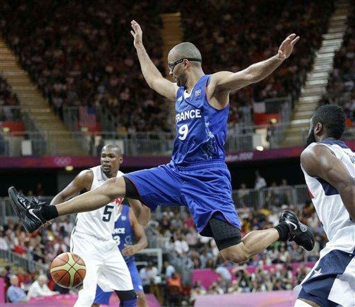 United States' James Harden, right, strips the ball from France's Tony Parker (9) during the first half of a preliminary men's basketball game at the 2012 Summer Olympics Sunday in London. Associated Press