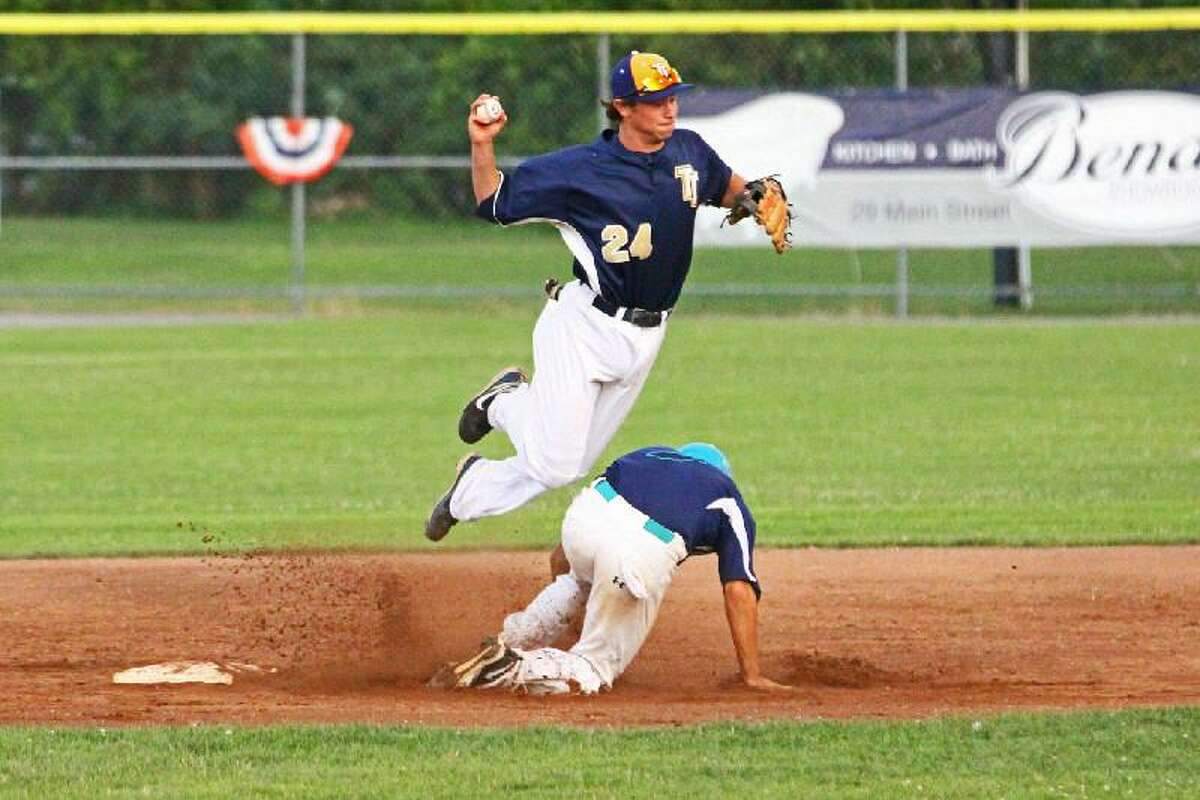 Register Citizen file art Torrington Titans second baseman Adam Claire leaps to get out of the way of an Old Orchard Beach baserunner while trying to turn a double play during a Tuesday night FCBL game at Fuessenich Park.