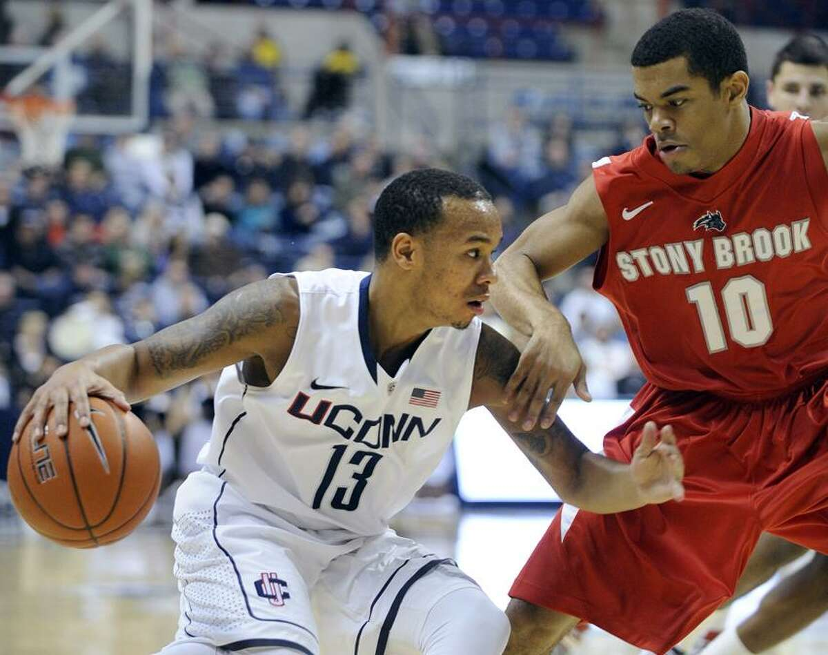 Connecticut's Shabazz Napier, left, drives past Stony Brook's Carson Puriefoy during the first half of Connecticut's 73-62 victory in an NCAA college basketball game, Sunday, Nov. 25, 2012, in Storrs, Conn. Nappier scored a game-high 19 in the victory. (AP Photo/Fred Beckham)