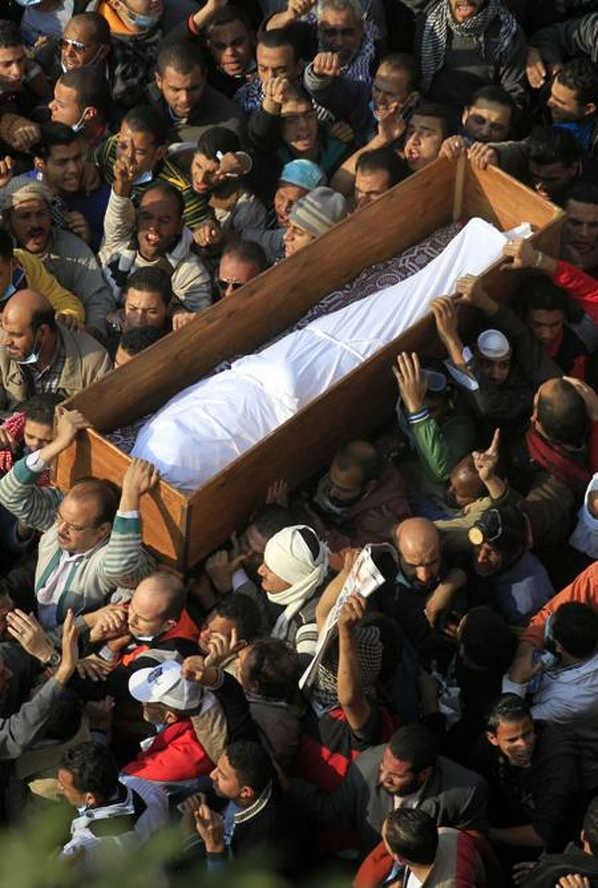Egyptians carry a body of a protester was killed in clashes with the Egyptian riot police during his funeral at Tahrir square in Cairo, Egypt, Tuesday, Nov. 22, 2011.Egypt's civilian Cabinet has offered to resign after three days of violent clashes in many cities between demonstrators and security forces, but the action failed to satisfy protesters deeply frustrated with the new military rulers. (AP Photo/Khalil Hamra)