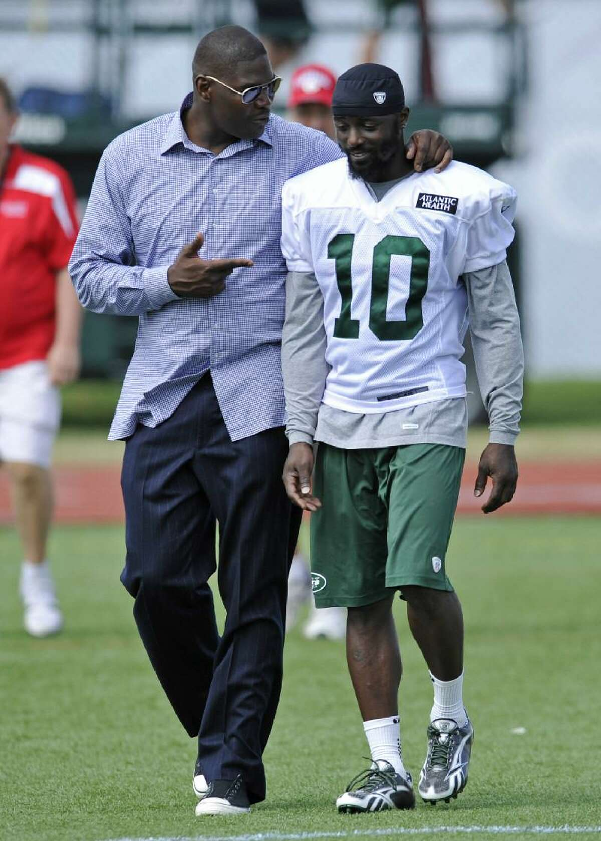 ASSOCIATED PRESS Former New York Jets receiver Keyshawn Johnson, left, talks with Jets wide receiver Santonio Holmes after practice on opening day of their training camp Friday in Cortland, N.Y.