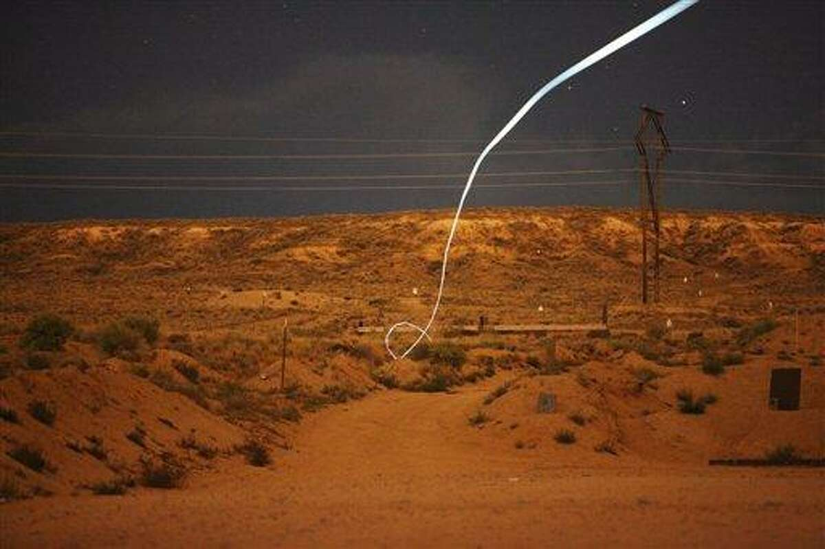 In this undated photo provided by Sandia National Laboratories, a time exposure, a light-emitting diode, or LED, attached to a self-guided bullet at Sandia National Laboratories shows a bright path during a nighttime field test. Associated Press