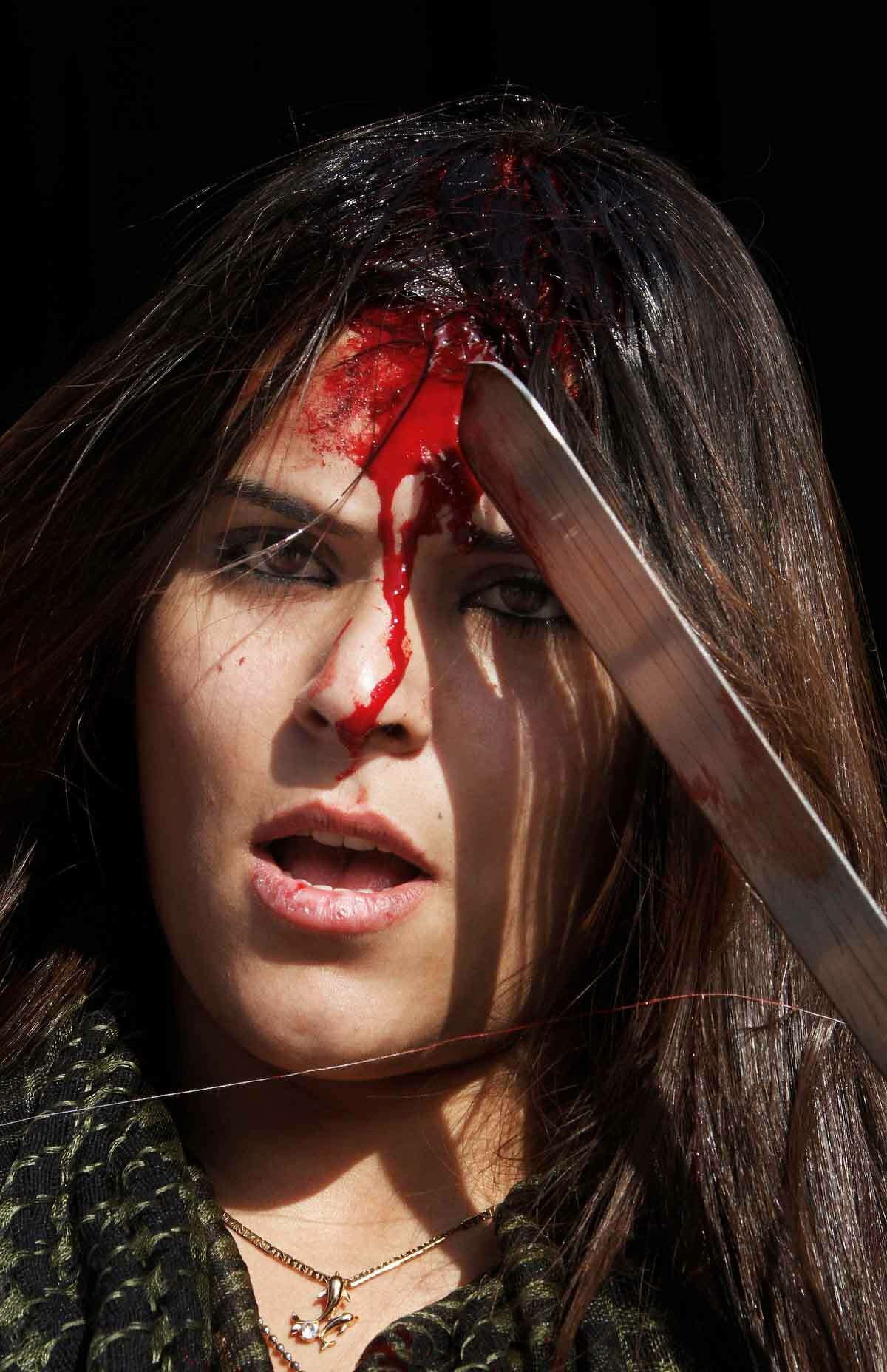 A Lebanese Shiite woman, bleeds from self inflicted wounds during Ashoura day in the southern market town of Nabatiyeh, Lebanon, Sunday Nov. 25, 2012. Ashoura day is the remembrance of the 680 A.D. battle in which their saint and grandson of Islam's prophet Muhammad, Hussein, was killed by rivals cementing the split in Islam between Shiites and Sunnis. (AP Photo/Mohammed Zaatari)