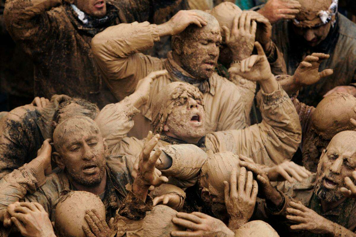 Iranian mourners cover themselves with mud, during Ashoura, marking the death anniversary of Imam Hussein, the grandson of Islam's Prophet Muhammad, at the city of Bijar, west of the capital Tehran, Iran, Sunday, Nov. 25, 2012. Hussein, one of Shiite Islam's most beloved saints, was killed in a 7th century battle at Karbala, Iraq. (AP Photo/Vahid Salemi)