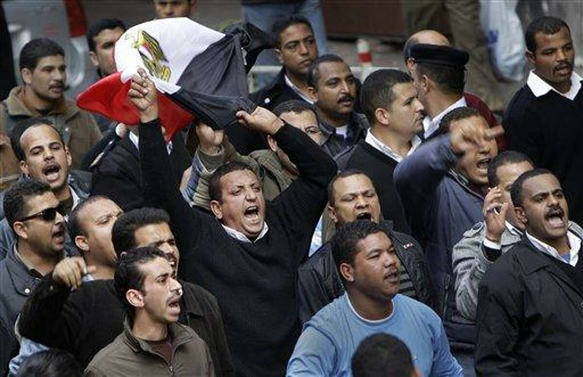 Egyptian police, one carrying an Egyptian flag, demonstrate outside the Interior Ministry near Tahrir Square in downtown Cairo, Egypt Sunday, Feb. 13, 2011. The police, hated for their brutality and corruption under decades-old emergency laws, marched Sunday through Tahrir Square to the Interior Ministry demanding better pay and conditions, but also sought to absolve themselves of responsibility for the police's attempted crackdown at the start of the protests that killed many demonstrators. (AP Photo/Ben Curtis)