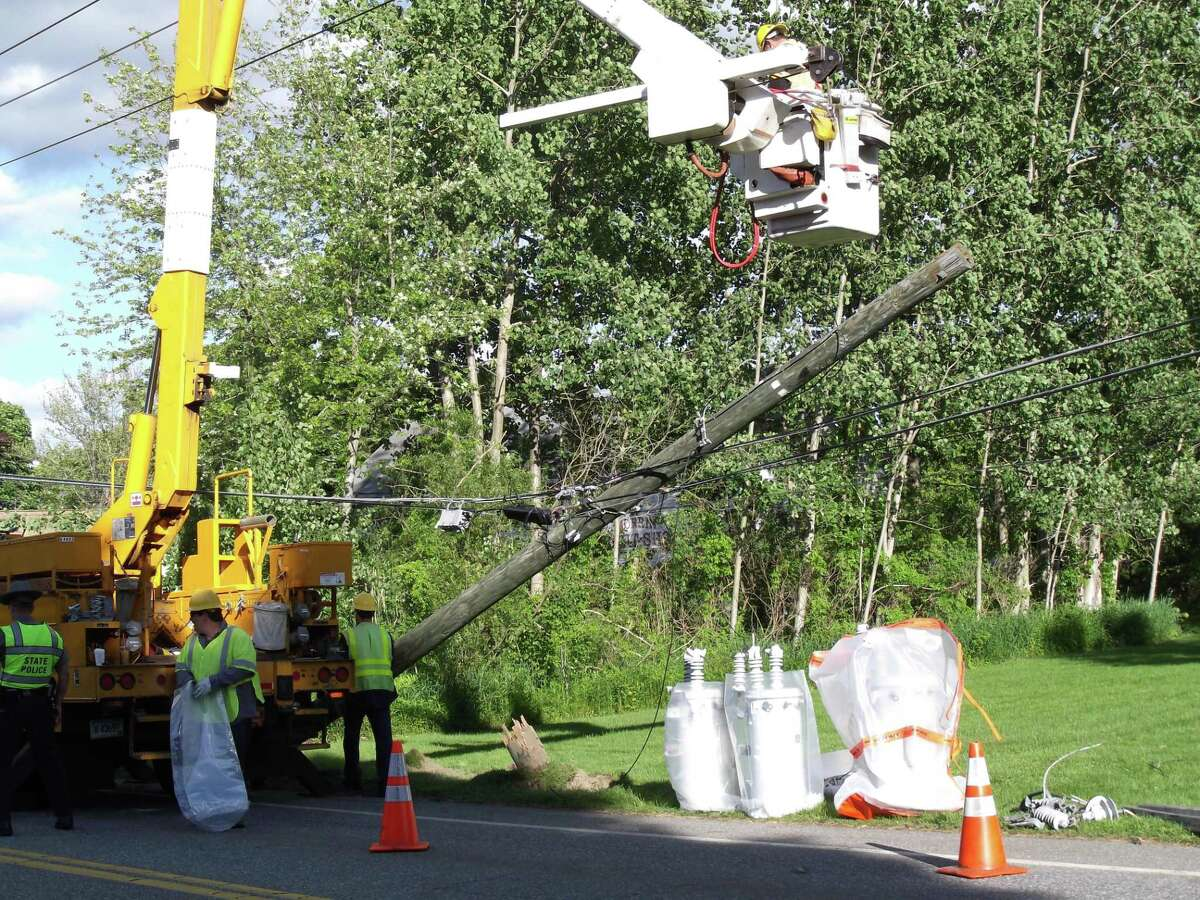 RICKY CAMPBELL/Register Citizen A power company crew works on Route 61 in Morris after winds knocked a pole and wires down, causing a power outage.