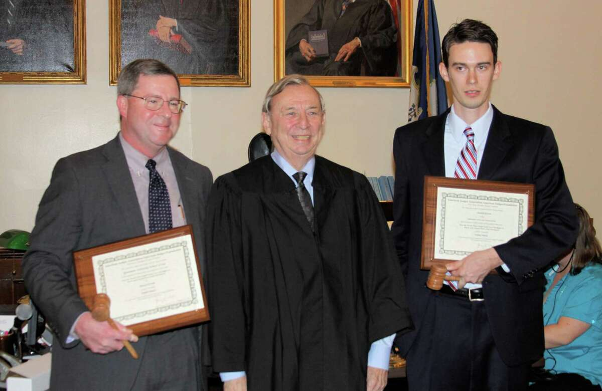 Photo by Kathryn Boughton Judge Charles Gill of Litchfield Superior Court, center, honored Quinnipiac University law student Daniel Erwin, right, and Quinnipiac law dean Brad Saxton, left, last Thursday afternoon.