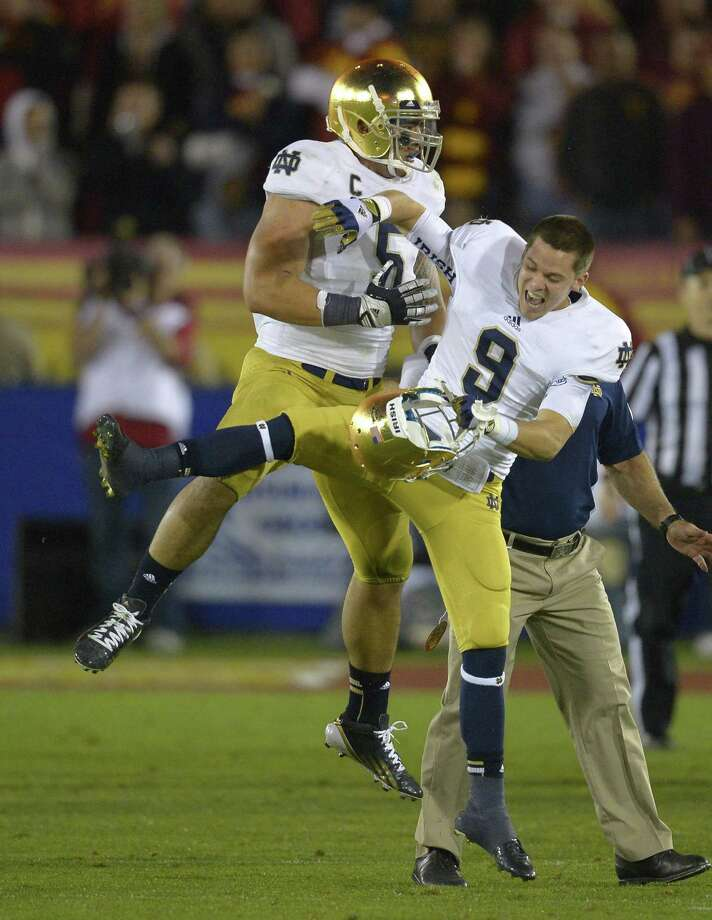 Notre Dame linebacker Manti Te'o, left, celebrates with Notre Dame wide receiver Robby Toma in the closing seconds of their game against USC. By The Associated Press Photo: ASSOCIATED PRESS / Mark J. Terrill2012