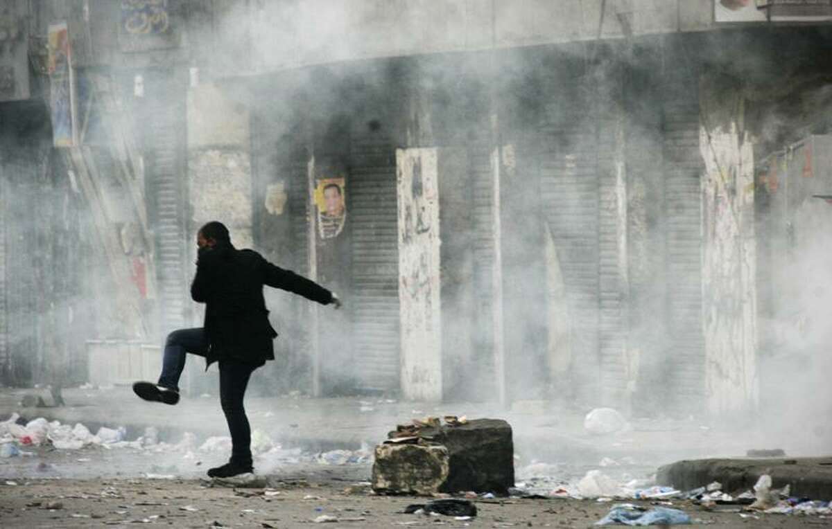 An Egyptian protester covers his face from tear gas during the clashes with Egyptian riot police, unseen, in Cairo, Egypt, Monday, Nov. 21, 2011. Egyptian riot police clashed Monday with thousands of protesters demanding that the ruling military quickly announce a date to hand over power to an elected government. (AP Photo/Mohammed Abu Zaid)