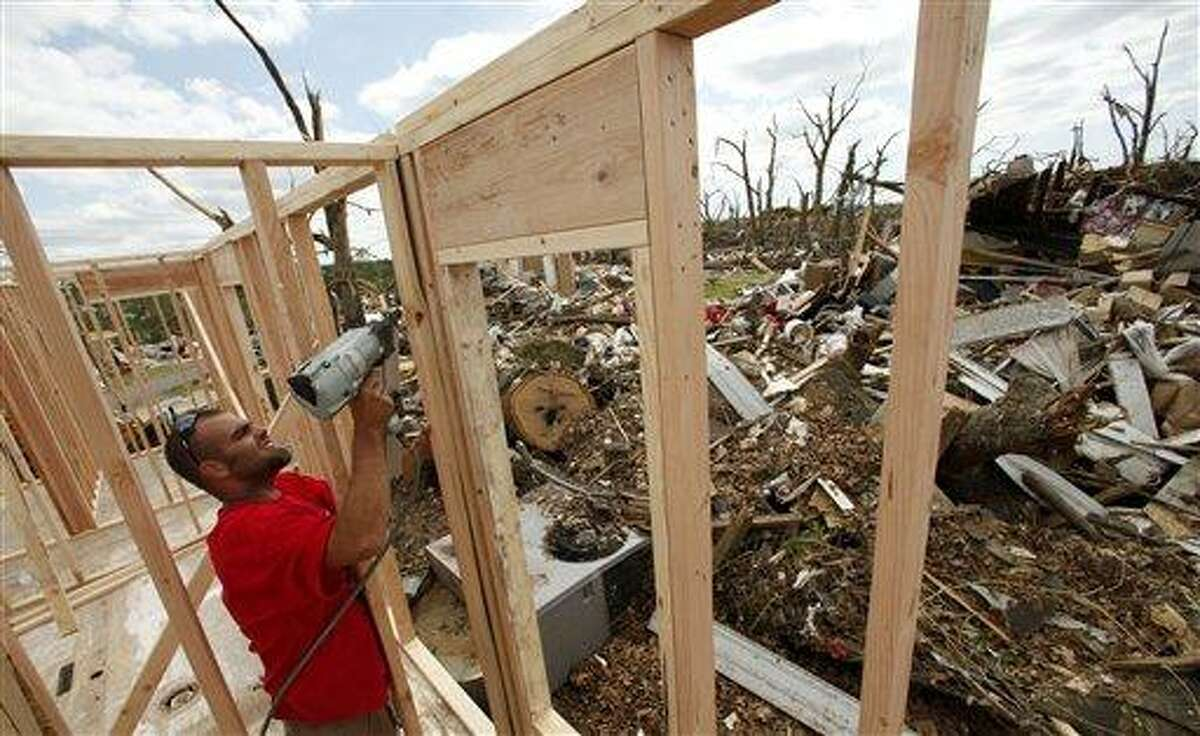 Phillip Law frames a wall as he helps rebuild a destroyed beauty salon in Joplin, Mo. Thursday, May 26, 2011. The business was destroyed by an EF-5 tornado which tore through much of the city Sunday, damaging a hospital and hundreds of homes and businesses and killing at least 125 people. The owner's husband, a general contractor rebuilding the shop, had planned to have the project finished in 45 days. (AP Photo/Charlie Riedel)
