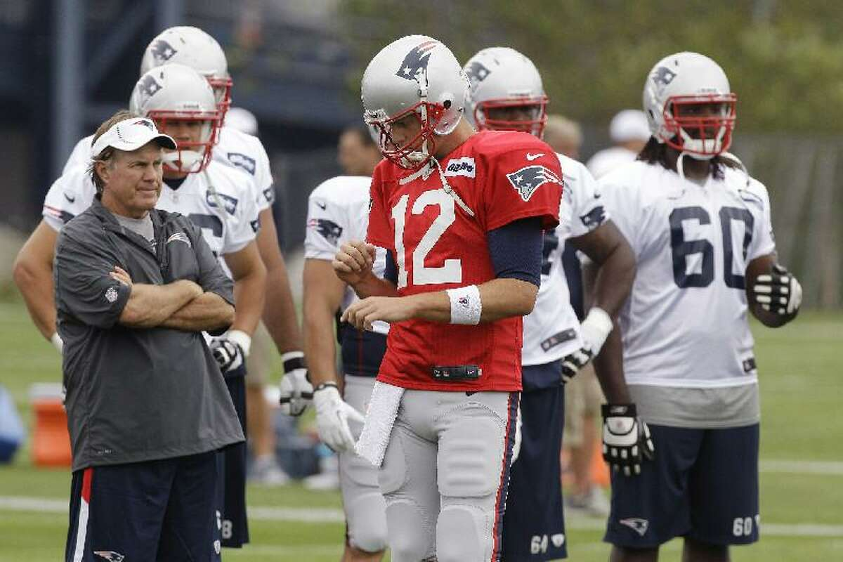 ASSOCIATED PRESS New England Patriots coach Bill Belichick looks over his practice field as quarterback Tom Brady (12) walks by during the first day of the team's training camp in Foxborough, Mass., Thursday.