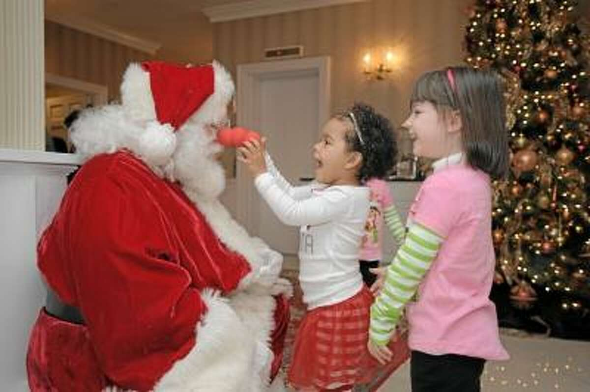 Photo by Laurie Gaboardi A member of the Connecticut Society of Santas charms his greatest fans, during the organization's annual meeting held recently at the Litchfield Inn.