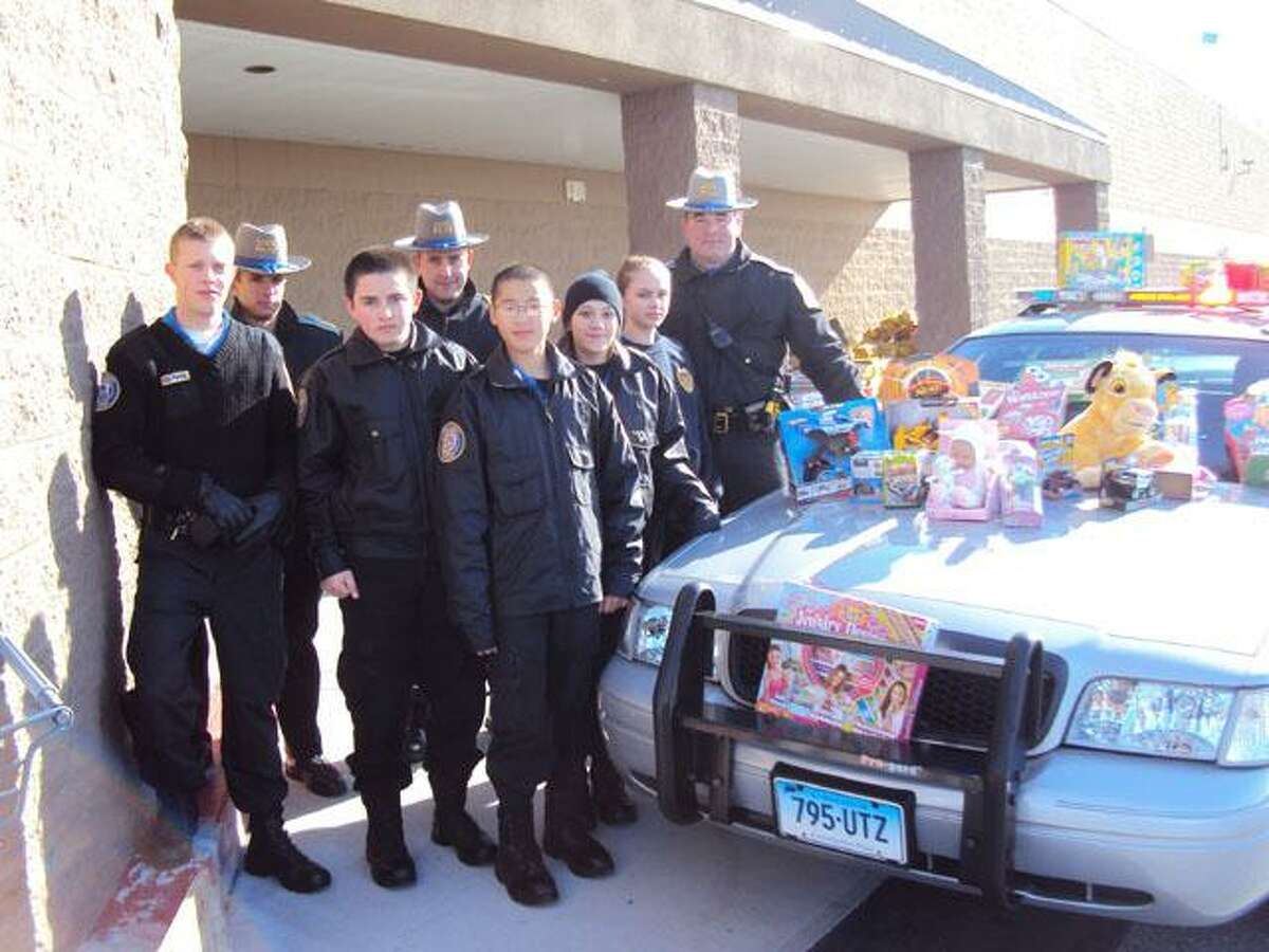 RICKY CAMPBELL/Register Citizen TORRINGTON - State Police Explorer/Cadets stand around a cruiser Saturday during their toy drive outside Wal-Mart on E. Main Street. Just a few feet away, other members were collecting food outside of Price Chopper.