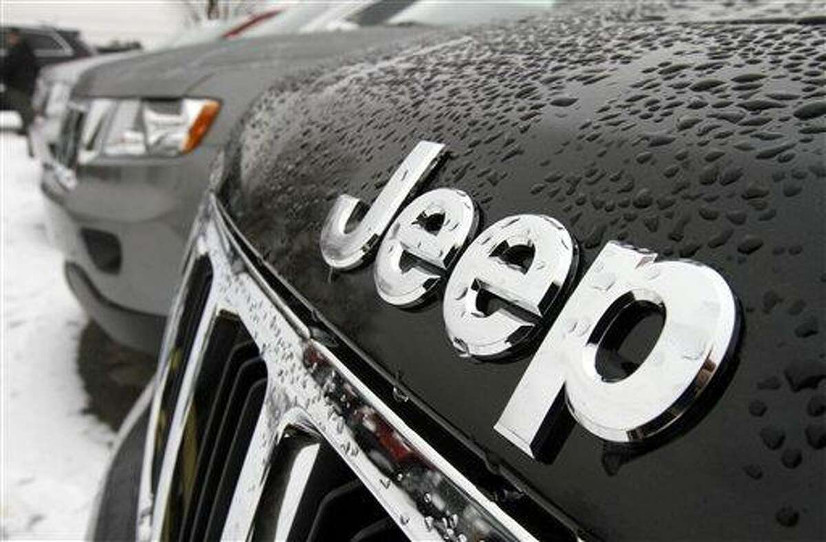 The Chrysler Jeep logo is displayed on a 2012 Jeep Grand Cherokee. Chrysler has posted its first annual net income since 1997. Associated Press