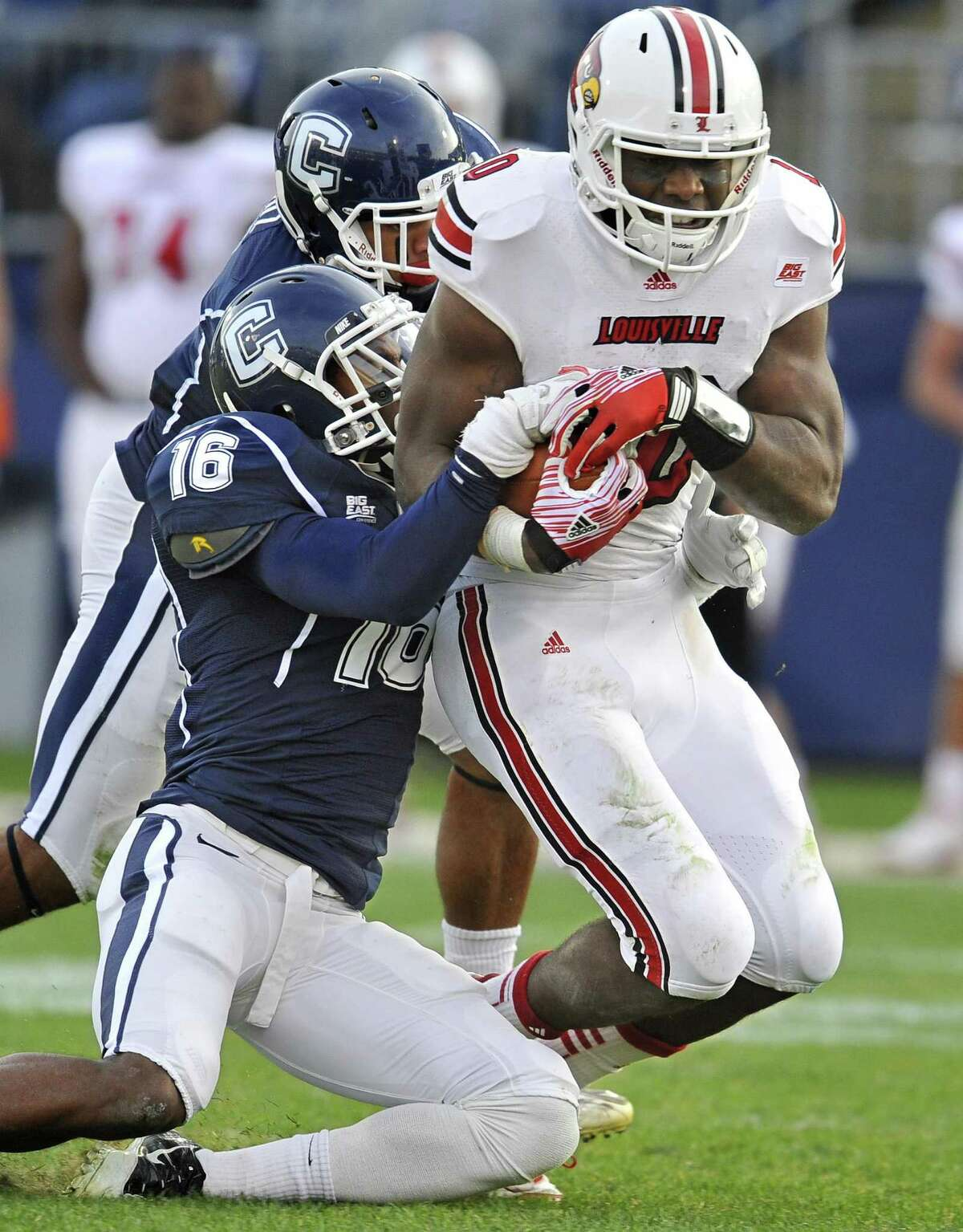 Louisville's Dominque Brown, right, gains yards while pursued by Connecticut's Byron Jones (16), and Dwayne Gratz, back, in the second half of an NCAA college football game at Rentschler Field in East Hartford, Conn., Saturday, Nov. 19, 2011. (AP Photo/Jessica Hill)