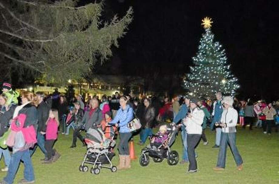 John Berry/Register Citizen Attendees of the Light Up Main event on Friday make their way from the tree in Coe Memorial Park toward the next event as the procession made stops all the way up Main Street in Torrington.