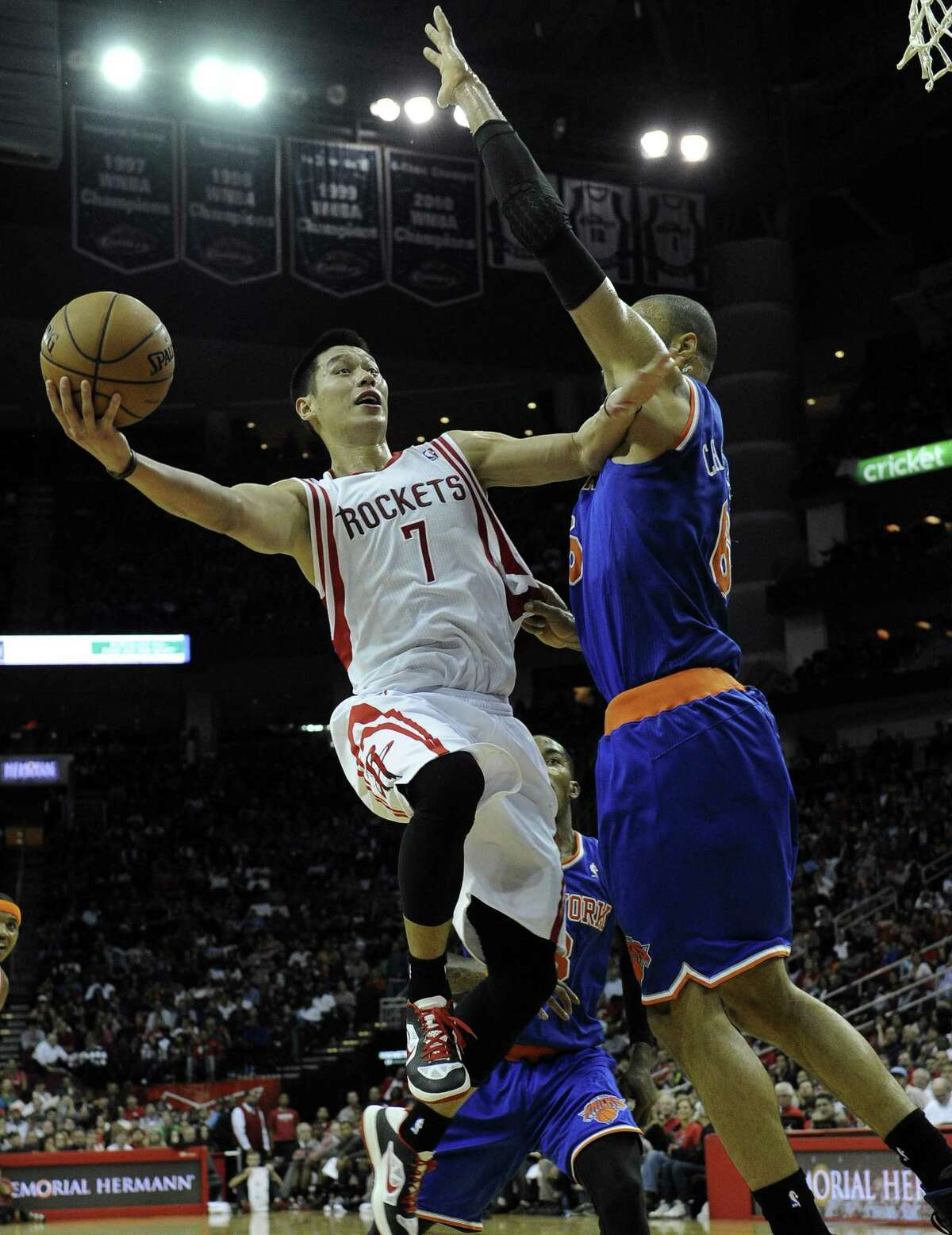 Houston Rockets guard Jeremy Lin attempts a lay-up around New York Knicks center Tyson Chandler. By Associated Press