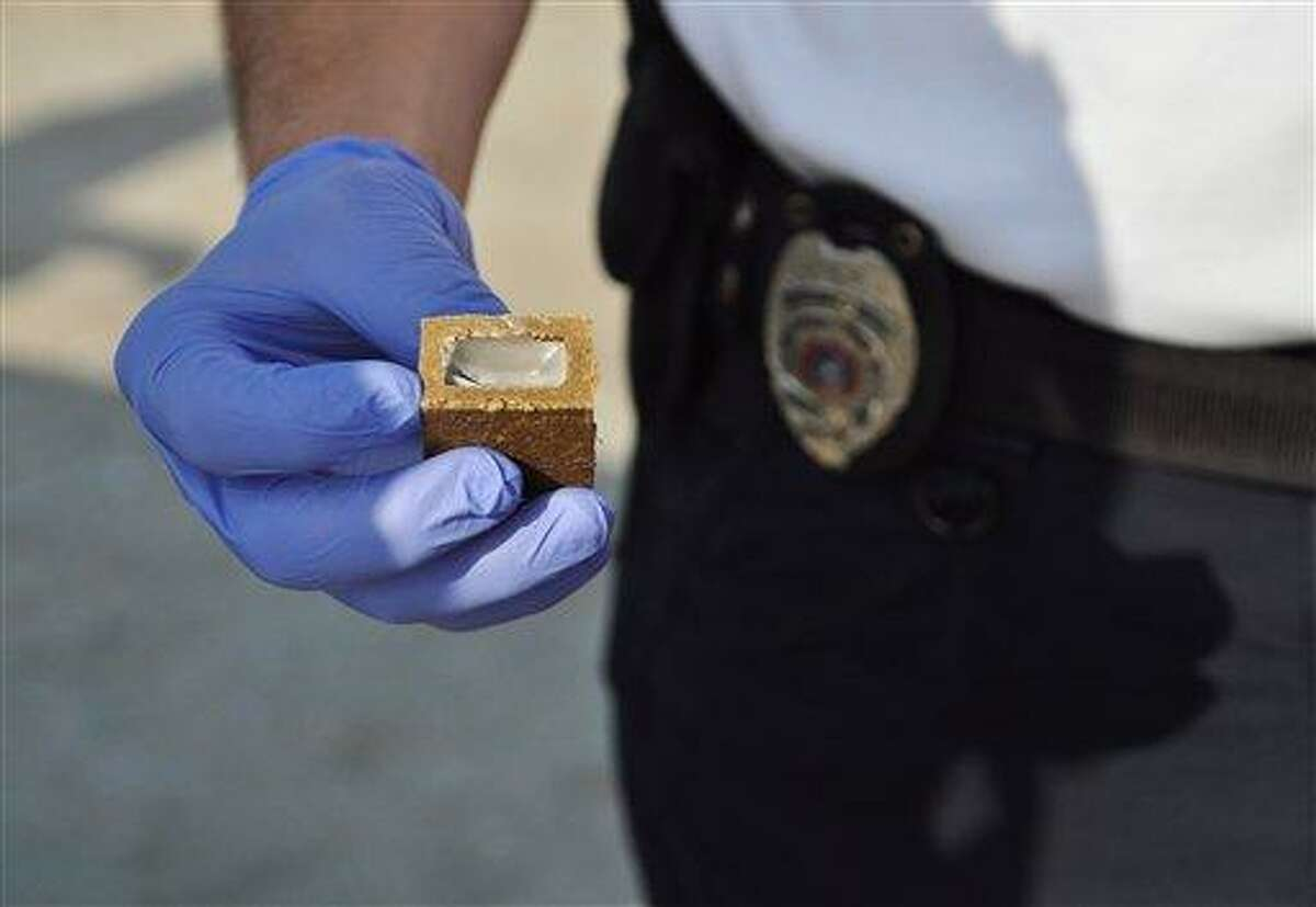 An animal control officer from Texas holds up a piece of vaccine bait, which health officials hope will curb rabies outbreaks nationwide. A vaccine capsule is hidden within a small chunk of white wax, which is in turn surrounded by a hard cube made of fish meal. The pungent smell of the fishmeal attracts animals, which bite into the cubes, breaking open the vaccine capsules, and thus becoming innoculated. Associated Press