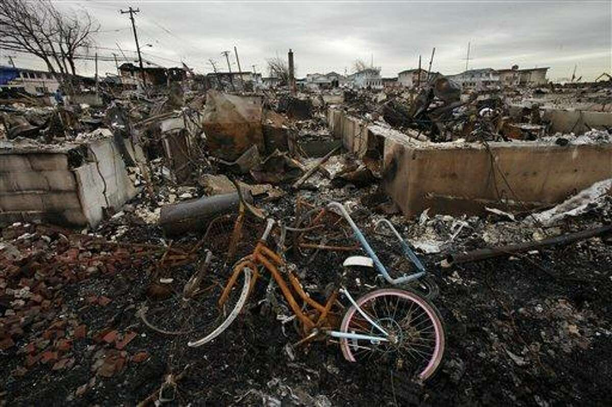 FILE - In this Nov. 13, 2012 file photo, a burned bicycle lies in the ashes of a burned out home in the Breezy Point section of the Queens borough of New York. More than 50 homes were lost in a fire that swept through the oceanside community during Superstorm Sandy. Some residents of New York City's storm-battered Breezy Point neighborhood say thieves looted their damaged houses over Thanksgiving. (AP Photo/Mark Lennihan, File)