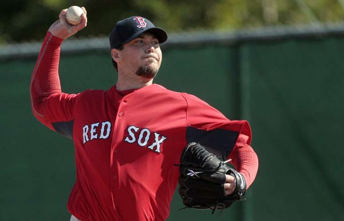 Boston Red Sox pitcher Josh Beckett throws at the Boston Red Sox player development complex in Fort Myers, Fla., Tuesday, Feb. 15, 2011. It was the first official spring training baseball workout for pitchers and catchers. (AP Photo/Dave Martin)