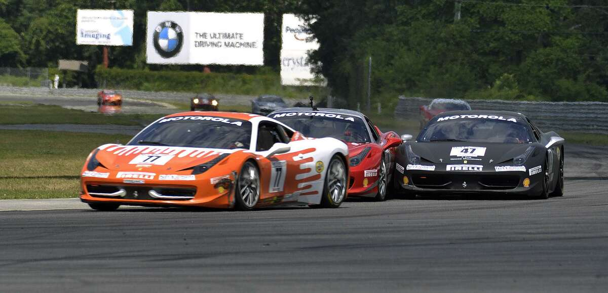RICK THOMASON/Register Citizen Right on the bumper of Harry Cheung (77), Darren Crystal (47) jams another driver in the first Ferrari Challenge 458/430 race Saturday at Lime Rock Park. Though they traded a little paint, both drivers finished the race, but well behind winner Enzo Potolicchio.