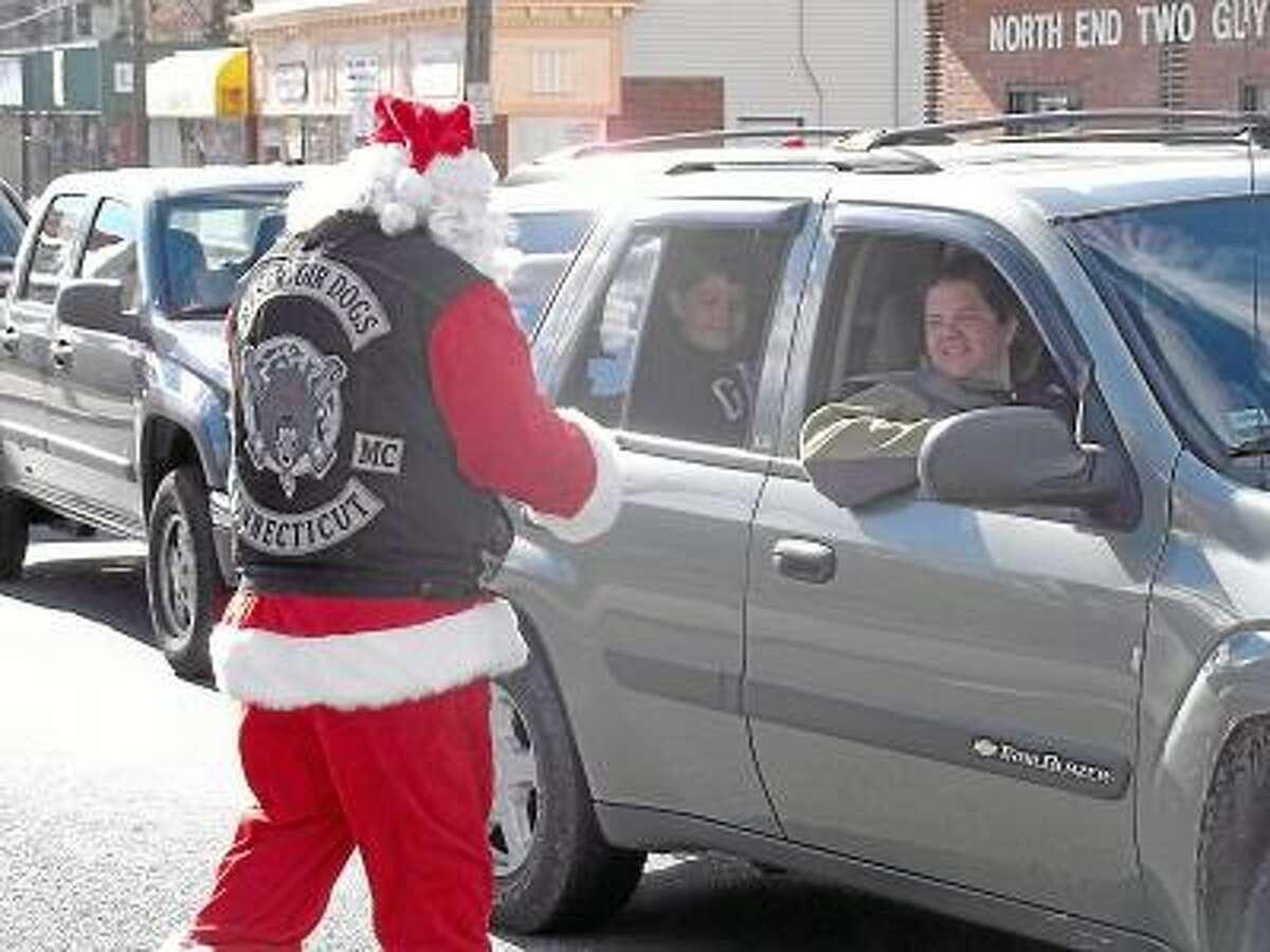 Santa Claus joined the one percenter bikers Saturday and put on his Reservoir Dogs vest for a good cause. The motorcylce club held its annual toy, food and money drive at the corner of Main and East Elm streets. RICKY CAMPBELL/ Register Citizen