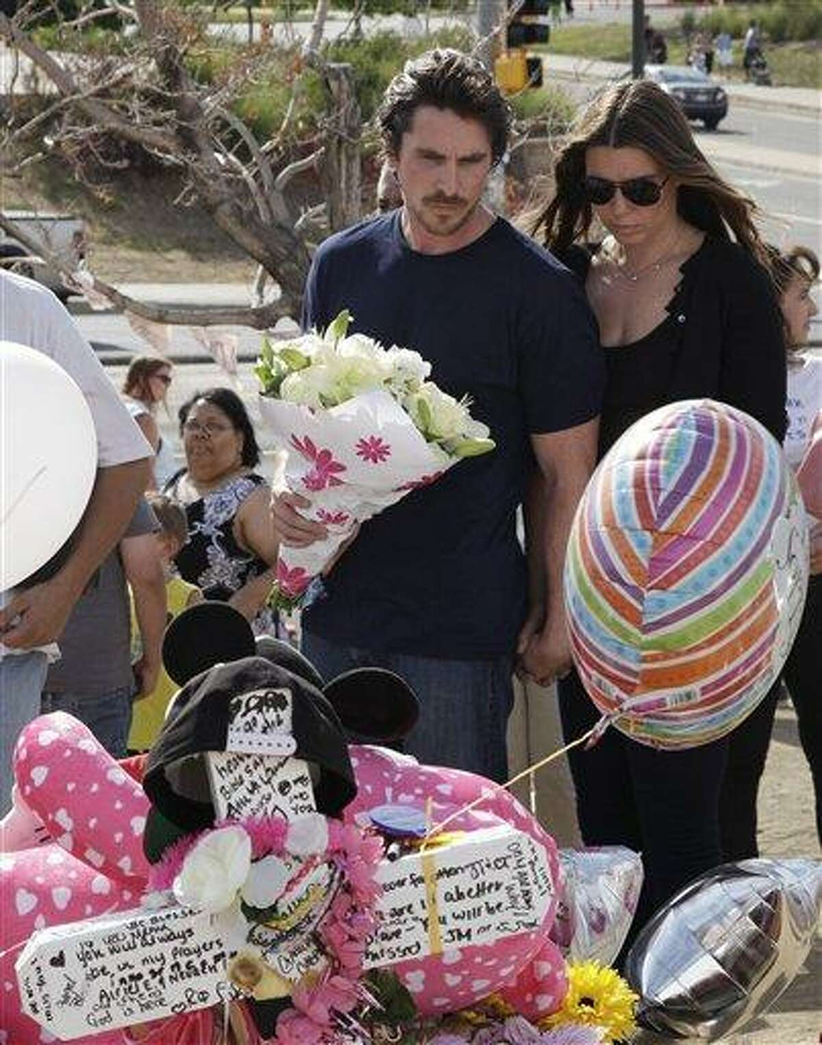 Actor Christian Bale and his wife Sibi Blazic carry flowers as they visit a memorial to the victims of Friday's mass shooting Tuesday in Aurora, Colo. Associated Press