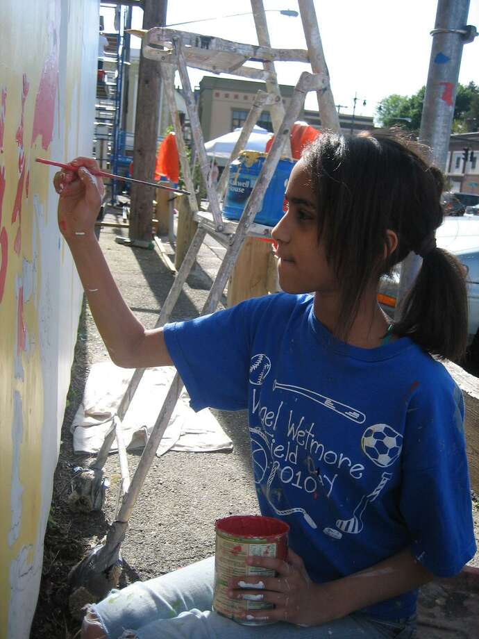 Yasmin Gutierrez paints a portion of a mural that is part of the Community Mural Project being offered by ASAP.
