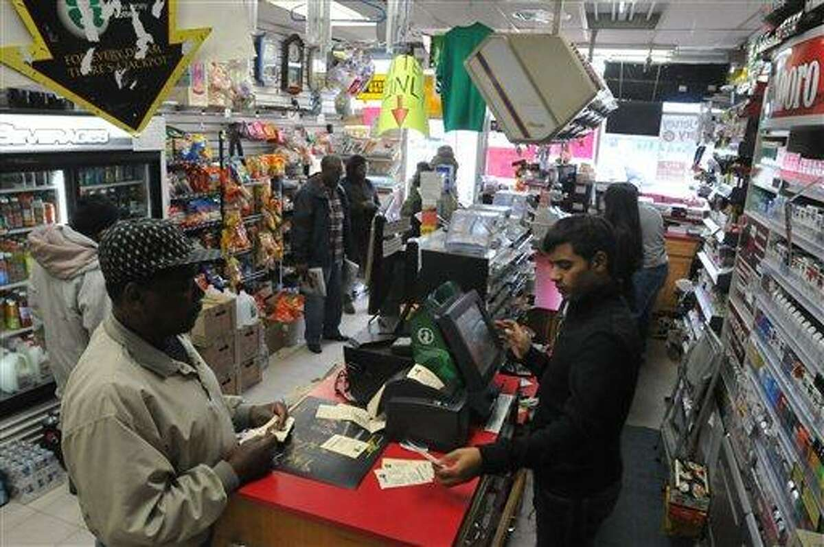 A customer purchases lottery tickets for the Powerball lottery at Foster Stationery in Bergenfield, N.J. on Saturday, Nov. 24, 2012. The jackpot for Powerball's weekend drawing has climbed to $325 million, the fourth-largest in the game's history. Powerball organizers say this is the first run-up to a large jackpot that's fallen over a major holiday. (AP Photo/The Record (Bergen County), Don Smith)