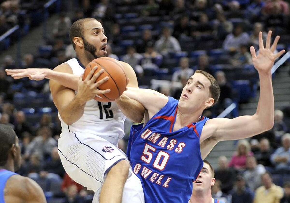 Connecticut's R.J. Evans, left, is fouled by Massachusetts Lowell's James McDonnell during the first half of an exhibition college basketball game in Hartford, Conn., Sunday, Nov. 4, 2012. (AP Photo/Fred Beckham)