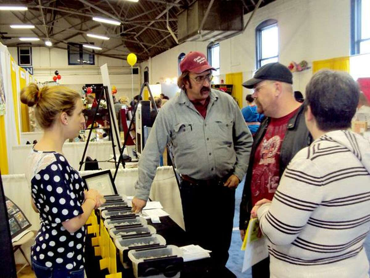 RICKY CAMPBELL/ Register Citizen Members of Mountaintop Trucking discuss business with visitors during Saturday's Home and Business Expo, an event by Northwest Connecticut's Chamber of Commerce. The expo featured more than 75 exhibitors Saturday, with the same number expected Sunday at the Torrington Armory.