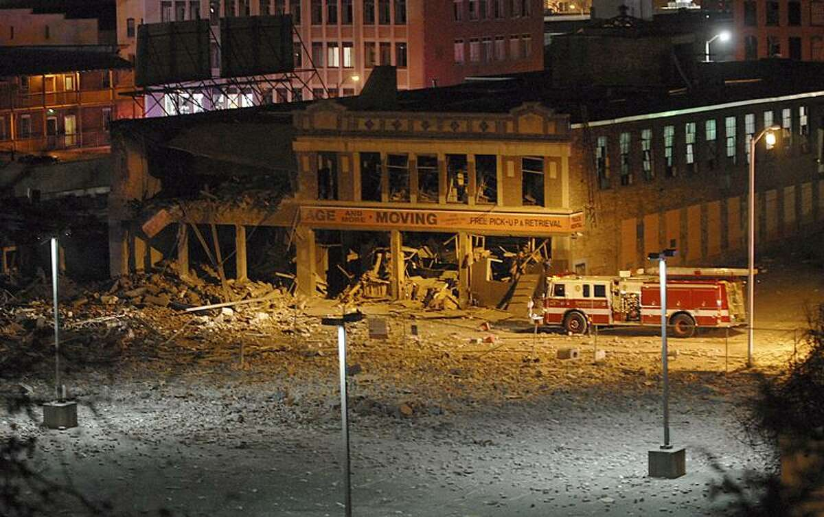 A firetruck is parked next to a damaged building after a nearby gas explosion leveled another building in downtown Springfield, Mass. on Friday, Nov. 23, 2012. (AP Photo/Springfield Republican, David Molnar)