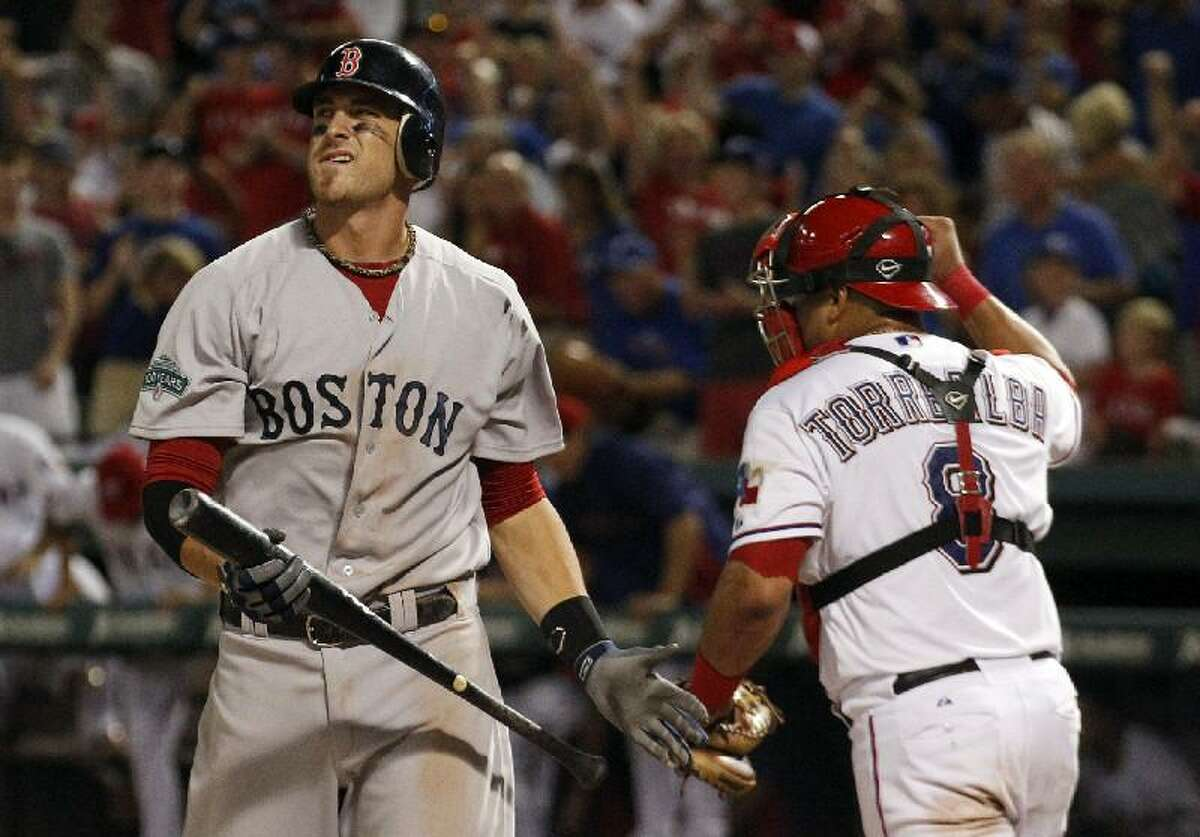 ASSOCIATED PRESS Boston Red Sox's Will Middlebrooks, left, heads back to the dugout after striking out against the Texas Rangers to end Wednesday night's game in Arlington, Texas. The Rangers won 5-4. The Ranger catcher is Yorvit Torrealba.