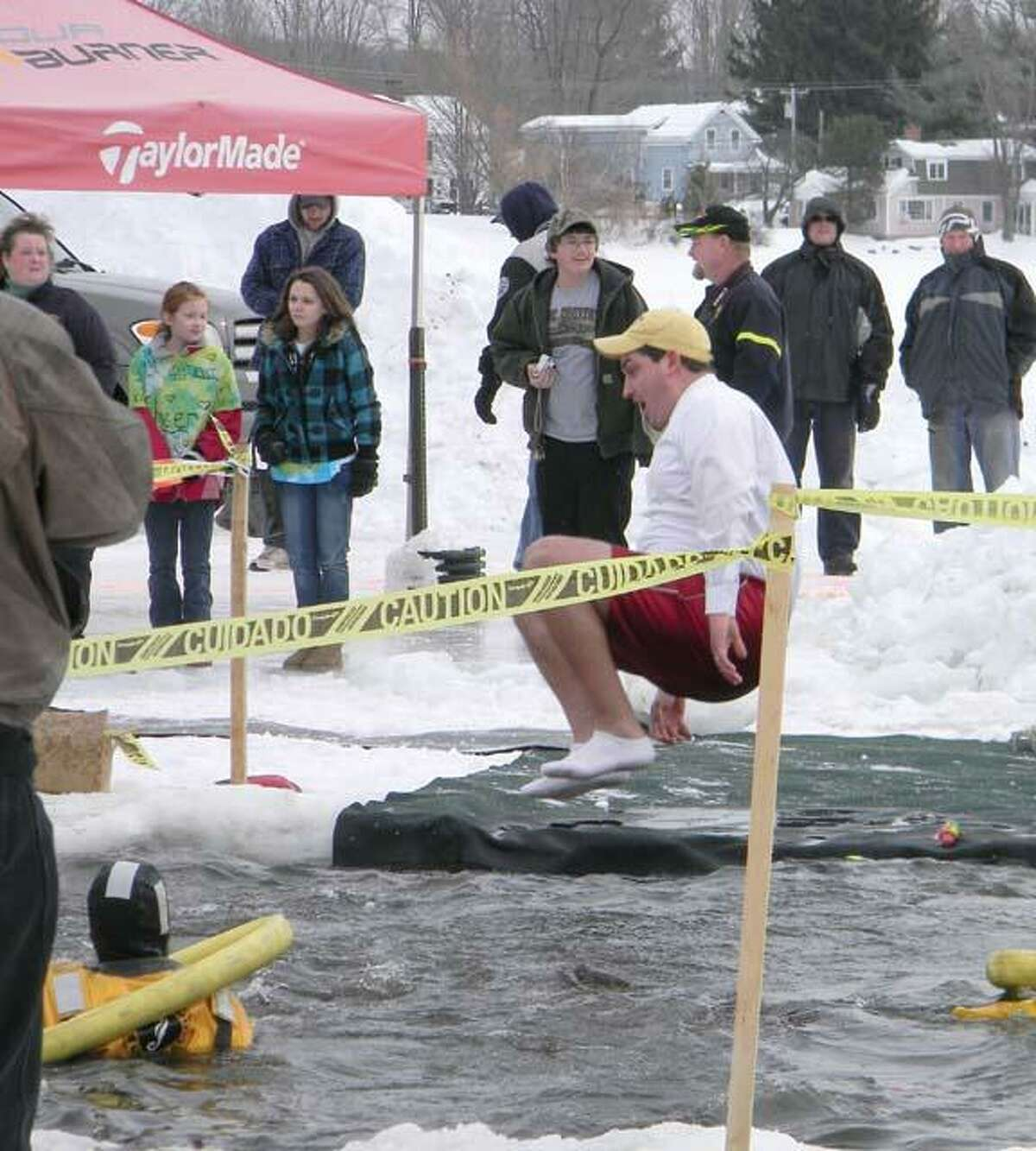 MIKE AGOGLIATI/ Register CitizenTorrington Mayor Ryan Bingham leaps into the freezing water of Highland Lake on Saturday. The mayor joined students from Torrington High School who participated in the Penguin Plunge in Winsted.