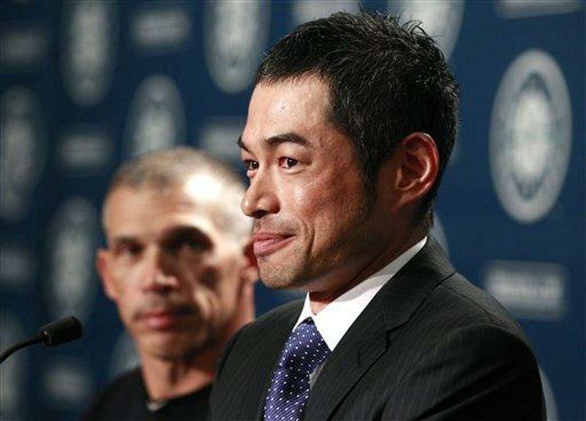 Ichiro Suzuki smiles as New York Yankees manager Joe Girardi, left, watches during a news conference, Monday, July 23, 2012, in Seattle. The Seattle Mariners announced that Suzuki, who has played with the Mariners since 2001, was traded to the Yankees for two young pitchers. (AP Photo/Elaine Thompson)