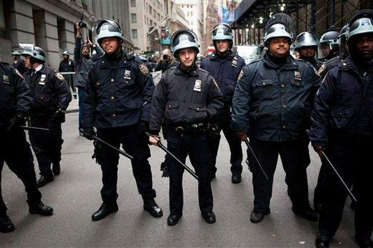 Police officers stand with their batons at the ready during a march of Occupy Wall Street protestors on the Financial District, Thursday, Nov. 17, 2011, in New York. Two days after the encampment that sparked the global Occupy movement was cleared by authorities, demonstrators marched through the financial district and promised mass gatherings in other cities. (AP Photo/John Minchillo)