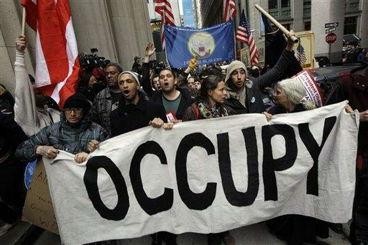 Demonstrators affiliated with the Occupy Wall Street movement march through the streets of the financial district, Thursday, Nov. 17, 2011 in New York. Two days after the encampment that sparked the global Occupy protest movement was cleared by authorities, demonstrators marched through New York's financial district and promised a national day of action with mass gatherings in other cities. (AP Photo/Mary Altaffer)
