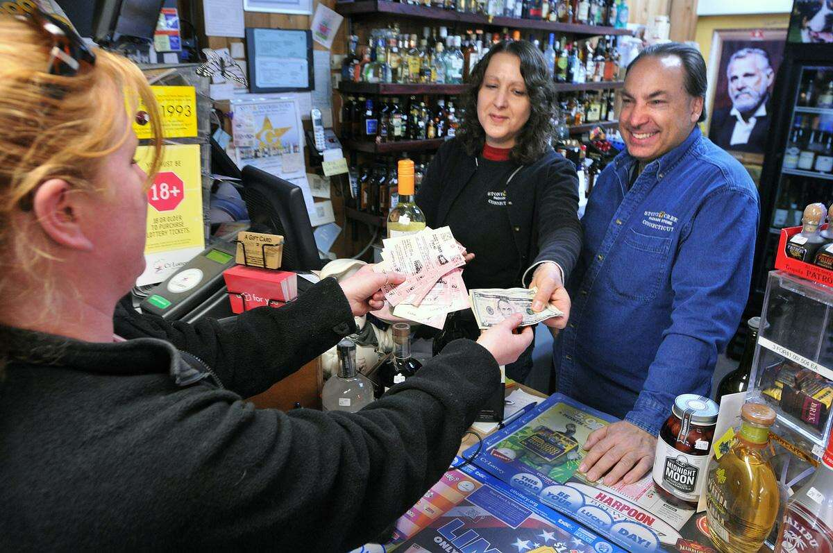 Emily Hayes of Stony Creek buys Mega Millions tickets Friday from owners Laura and Mark Richter at the Stony Creek Package Store. The $640 Million Mega Millions jackpot is the largest ever. Peter Casolino/Register
