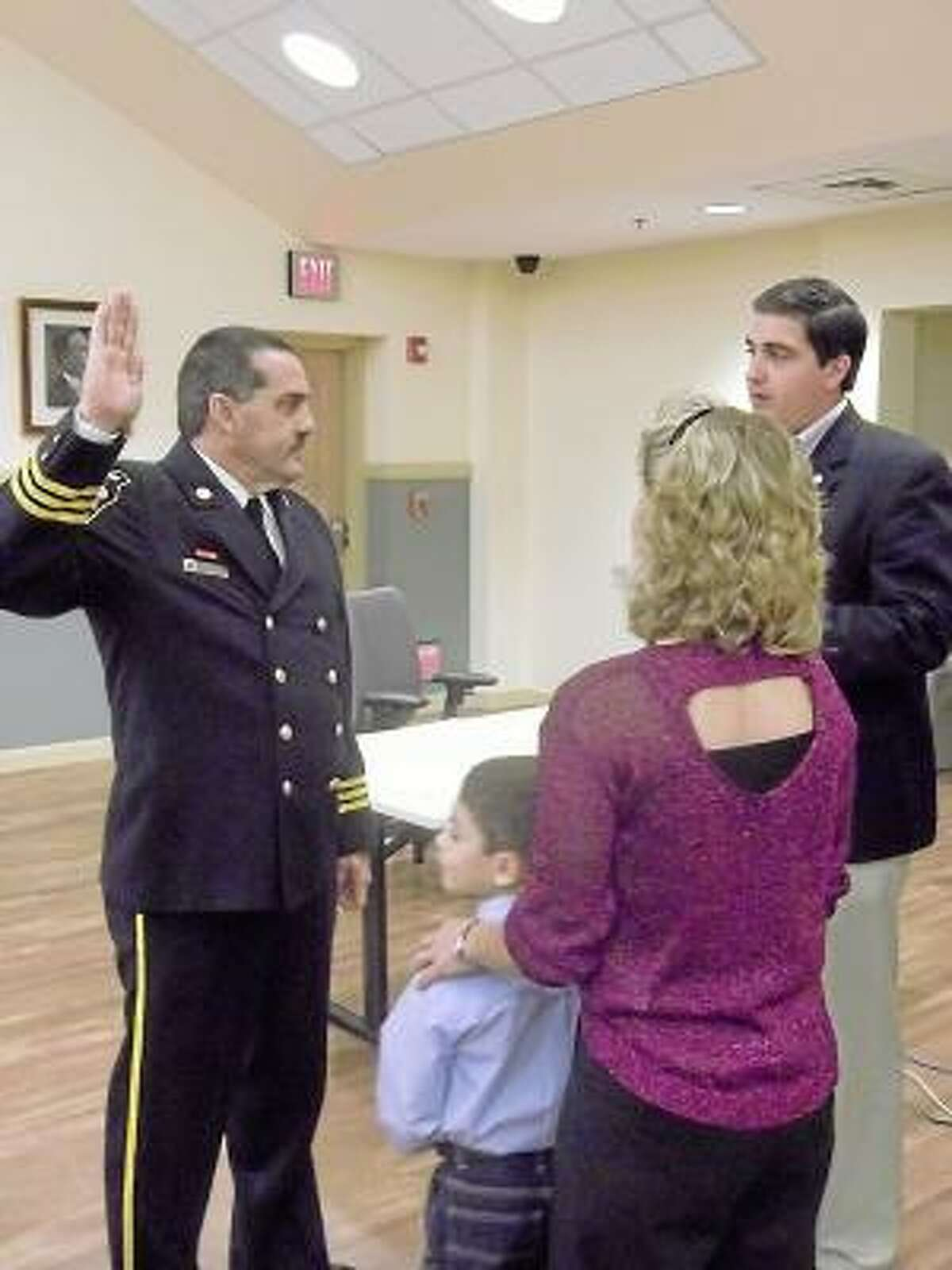 RICKY CAMPBELL/ Register Citizen Gary Brunoli was sworn in Wednesday night as Chief of Torrington Fire Department by Mayor Ryan Bingham. Brunoli's wife, Pam, and grandson Elias, 6, look on. Brunoli has been acting fire chief since July when his predecessor John Field left.